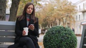 A mulher de negócio usa o telefone celular e o café da bebida no banco filme