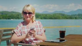 A mulher de negócio usa um smartphone em férias Assento em uma tabela em um café perto do lago em um fundo das montanhas dentro video estoque