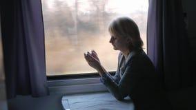 A mulher de negócio usa um smartphone, viaja em um compartimento do trem video estoque