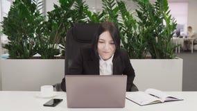 A mulher de negócio vê a boa notícia no portátil, nos risos e no júbilo no sucesso filme