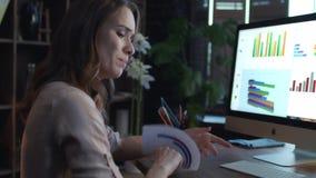 Mulher de negócio virada que trabalha com dados econômicos no computador na noite vídeos de arquivo