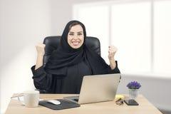 Mulher de negócios árabe nova que expressa o sucesso no escritório Imagens de Stock Royalty Free