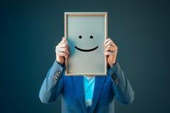 A mulher de negócios é otimista, guardando o emoticon do smiley sobre a cara Imagem de Stock Royalty Free