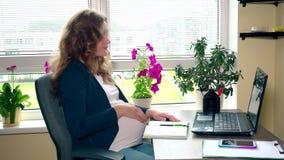 Mulher de negócios adulta grávida que trabalha em seu lugar de funcionamento no escritório vídeos de arquivo