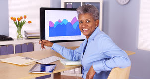 Mulher de negócios africana superior feliz que senta-se na mesa fotografia de stock