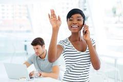 Mulher de negócios afro-americana de sorriso que acena ao falar no telefone celular imagens de stock