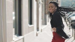 Mulher de negócios afro-americano feliz nova nos fones de ouvido que anda a rua da cidade ao escutar a música no video estoque