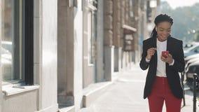 Mulher de negócios afro-americano feliz nova nos fones de ouvido que anda a rua da cidade ao escutar a música no filme
