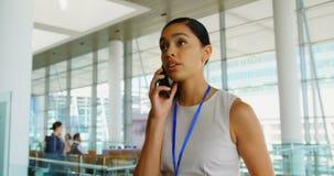 Mulher de negócios afro-americano nova bonita que fala no telefone celular no escritório 4k video estoque