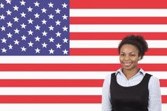 Mulher de negócios afro-americano nova que sorri sobre a bandeira americana fotos de stock