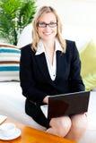 Mulher de negócios alegre com vidros usando seu portátil Fotos de Stock Royalty Free