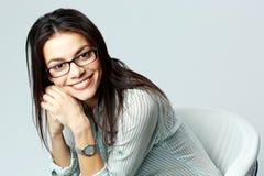 Mulher de negócios alegre nova que siiting na cadeira Fotografia de Stock