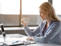 Mulher de negócios alegre que aprecia a ruptura de café imagem de stock
