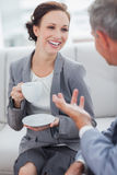 Mulher de negócios alegre que come o café com seu workmate Fotos de Stock Royalty Free