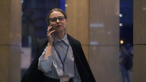 Mulher de negócios alegre que fala no telefone que anda em nivelar a rua vídeos de arquivo