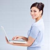 Mulher de negócios alegre que usa um portátil imagem de stock royalty free