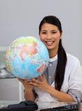 Mulher de negócios asiática assertiva que prende um globo imagem de stock
