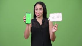 Mulher de negócios asiática bonita nova que guarda o sinal de papel do telefone e do selfie filme