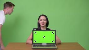 Mulher de negócios asiática bonita nova que mostra o portátil com o homem novo que passa perto video estoque