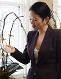 Mulher de negócios asiática bonita que admira plantas do escritório Imagem de Stock