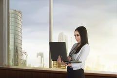 Mulher de negócios asiática bonita que guarda o portátil Fotografia de Stock