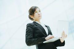 Mulher de negócios asiática fêmea atrativa que guarda um portátil Fotografia de Stock Royalty Free