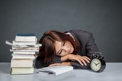 A mulher de negócios asiática fica cansado a leitura de muitos livros Foto de Stock Royalty Free