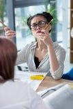 Mulher de negócios asiática nos monóculos que guardam lápis e que olham acima Fotografia de Stock Royalty Free