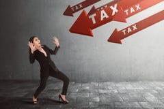 Mulher de negócios asiática nova chocada com imposto na seta que vai para baixo Imagens de Stock