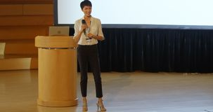 Mulher de negócios asiática nova que fala no orador na fase no auditório 4k filme