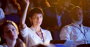 Mulher de negócios asiática nova que levanta a mão no seminário do negócio no auditório 4k filme