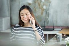 Mulher de negócios asiática nova que usa o smartphone para interagir com o cust fotografia de stock royalty free