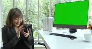 Mulher de negócios asiática para usar seu smartphone no escritório filme