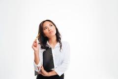 Mulher de negócios asiática pensativa bonita que guarda a prancheta e que pensa sobre algo imagens de stock