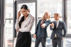 Mulher de negócios asiática que está no escritório, nos homens de negócios atrás de gesticular e no riso imagem de stock royalty free