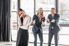 Mulher de negócios asiática que está no escritório, nos homens de negócios atrás de gesticular e no riso imagem de stock