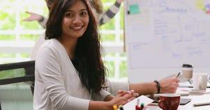 Mulher de negócios asiática que olha o olhar fixo na câmera