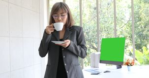 Mulher de negócios asiática que relaxa no escritório filme