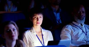 Mulher de negócios asiática que senta-se com o portátil no seminário do negócio no auditório 4k vídeos de arquivo