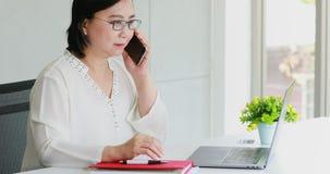 Mulher de negócios asiática que usa o telefone celular no escritório filme