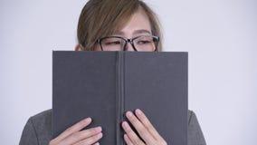 Mulher de negócios asiática tímida nova que pensa ao cobrir a cara com o livro vídeos de arquivo