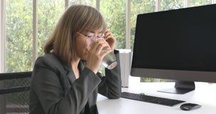 A mulher de negócios asiática toma a água da medicina e da bebida filme