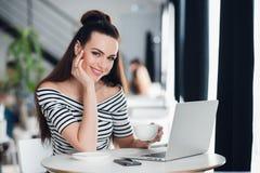 A mulher de negócios atrativa adulta está trabalhando em seu portátil em um café, jovem mulher de sorriso está usando um portátil Fotografia de Stock Royalty Free