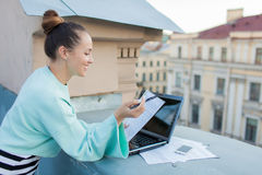 A mulher de negócios atrativa e à moda prepara originais para o telhado da casa na cidade velha que está atrás de um portátil Fotos de Stock Royalty Free