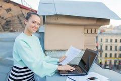 A mulher de negócios atrativa e à moda prepara originais para o telhado da casa na cidade velha que está atrás de um portátil Imagem de Stock Royalty Free