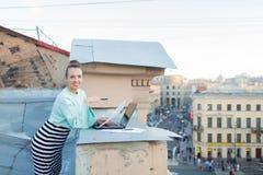 A mulher de negócios atrativa e à moda prepara originais para o telhado da casa na cidade velha que está atrás de um portátil Fotografia de Stock Royalty Free