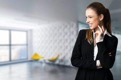 Mulher de negócios atrativa na frente de uma cena do escritório imagem de stock