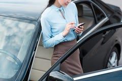 Mulher de negócios atrativa nova que inclina-se em um carro com estar aberto e datilografia fotografia de stock royalty free