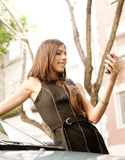 Mulher de negócios que inclina-se no carro com smartphone. imagens de stock