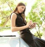 Mulher de negócios que inclina-se no carro com smartphone. Fotografia de Stock